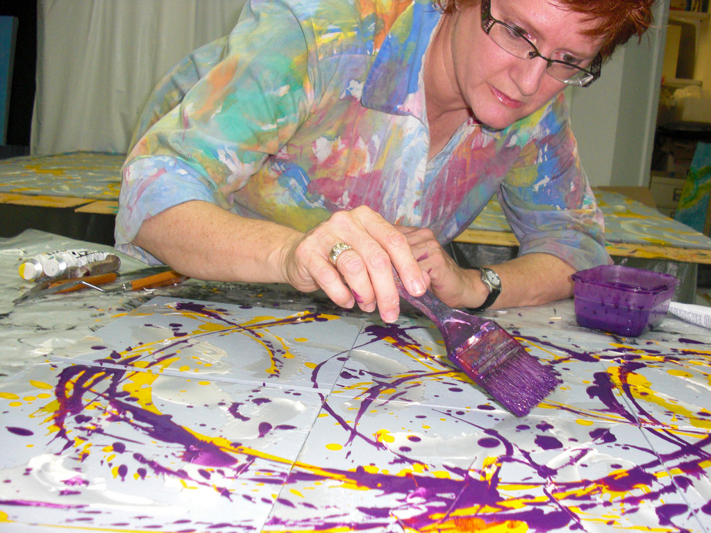 "Artist Alli Berman at work on one of her paintings. Her creations are on display at Long Island Children's Museum, in the exhibition ""Swirls, Waves & Puzzles."""