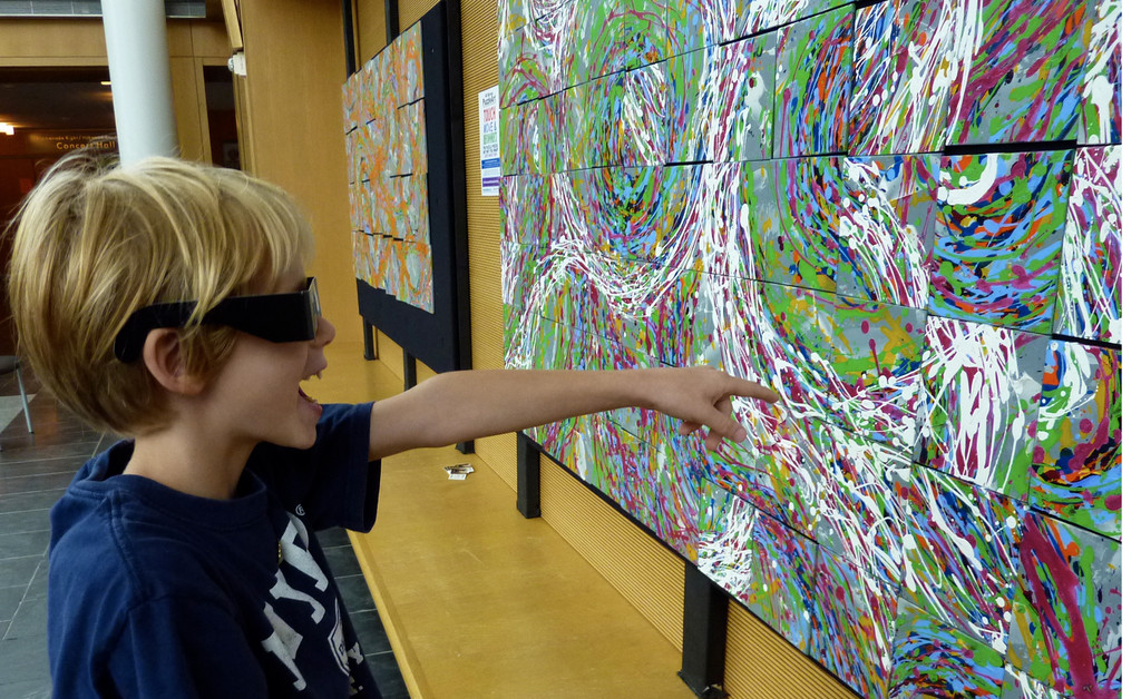 A visitor to Long Island Children's Museum uses 3D glasses to explore this unique exhibit featuring Alli Berman's interactive PuzzleArt.