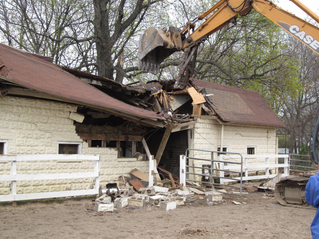 A backhoe slammed into the main barn at Lakewood Stables, demolishing it in a matter of minutes.