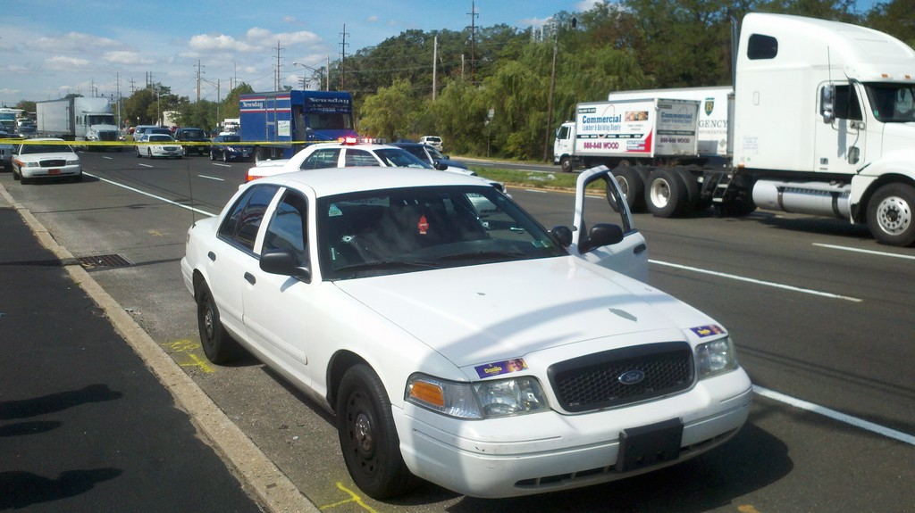 The suspects' Ford Crown Victoria with two bullet holes in the front window and one in the back, on Sunrise Highway in Wantagh.