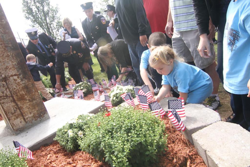 Children and adults placed American flags around the memorial where the steel from the Twin Towers was installed.