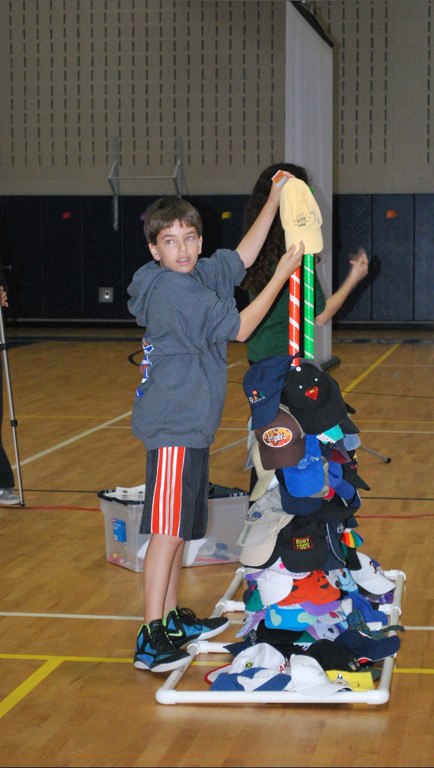 "Woodmere Middle School eighth-grader Mason Fliesel placed a hat on a pole during the ""Stack the Caps"" assembly."