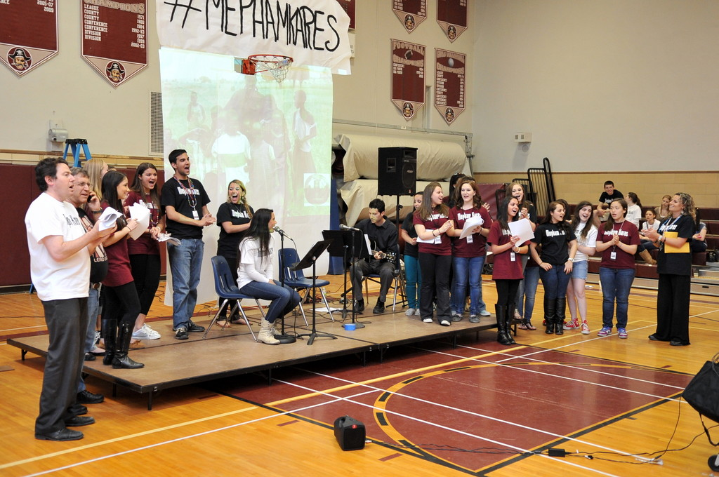 "Mepham High School students and faculty members joined junior Brenna Sherlock on stage during her rendition of ""Lean on Me"" at Mepham's Night of Action to benefit L.E.A.D. Uganda, a nonprofit charitable organization."