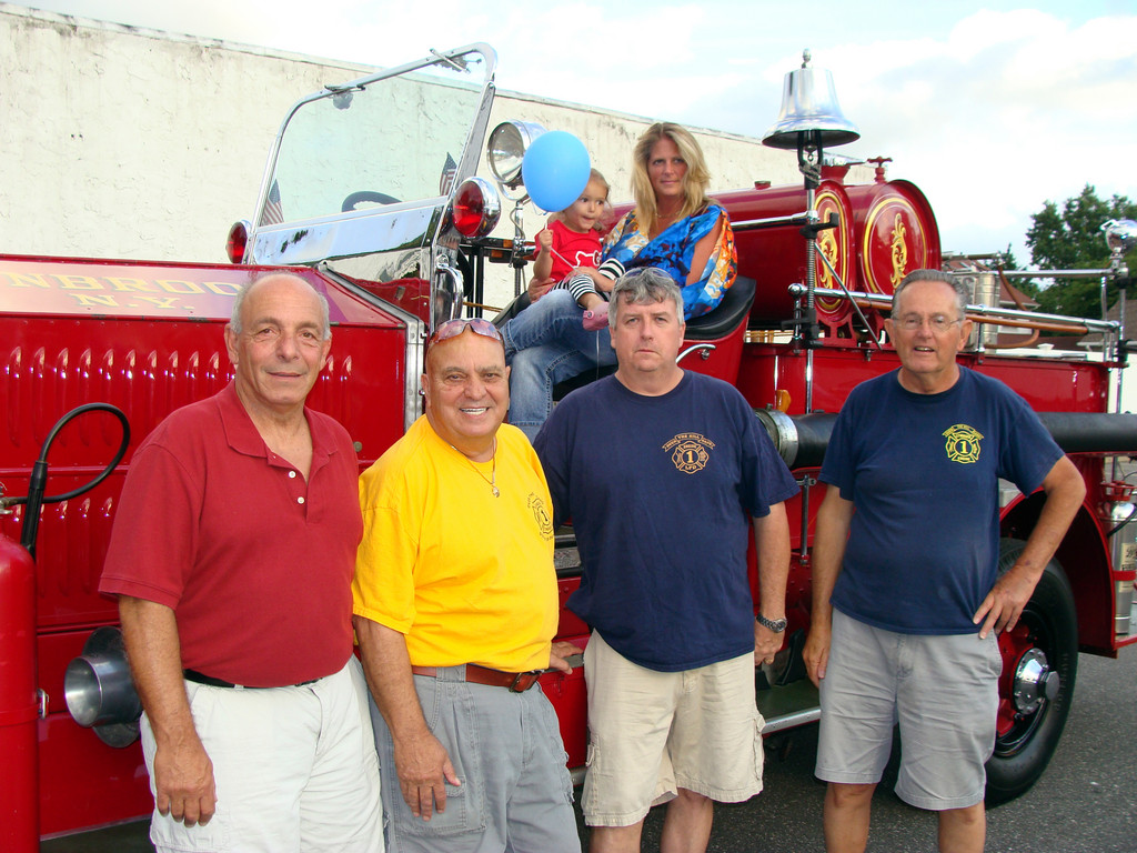 Car show coordinator Rich Cittadino, left, in front of an antique Lynbrook Engine No. 1 truck and LFD's Tony Badolato, John O'Reilly and Jack Callanan. Sitting in the truck were Crystal Albert with Nicolette Killibride, 3.