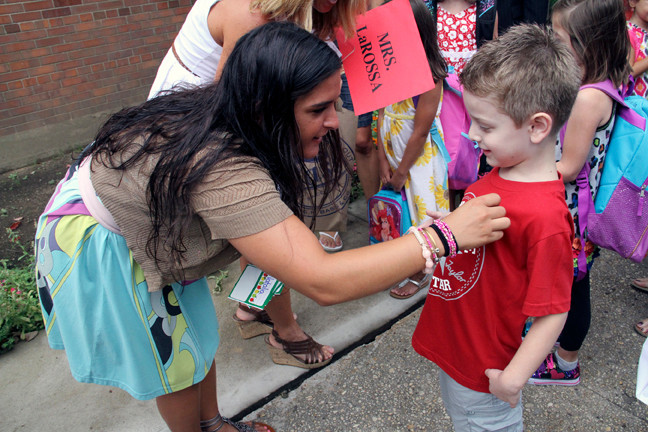 Miss Cutrone gives kindergartner Aaron Dito his name tag at Polk Avenue.