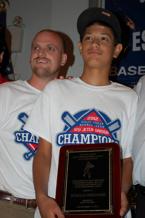 Nicholas Hernandez received his player of the year award in the Derek Jeter Division from coach Matt Roth.