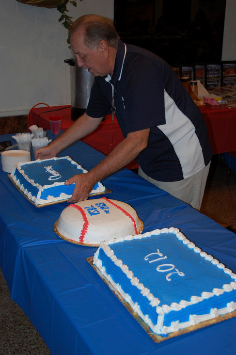 League Vice PResident Richard Graves puts out the cakes to celebrate a successful baseball season.