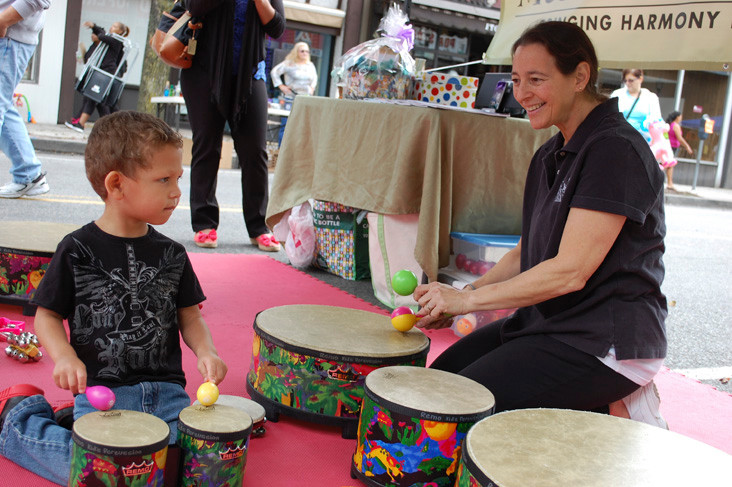 Kai Moy, 2, got to play along right on the street with Sheri Zuckerbot from Music Together, an early childhood music and movement program.