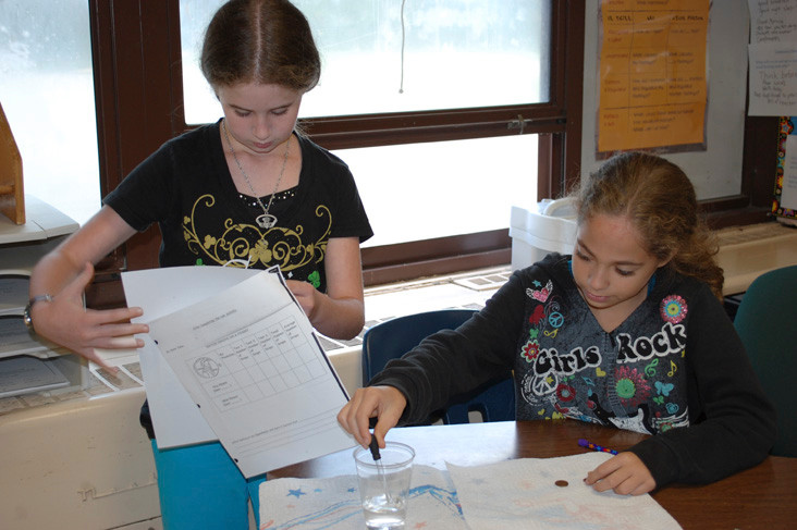 Erin Laxton and Haley DelGadillo, sixth graders at the William L. Buck School, conduct a science experiment where they find out how many drops of water an old penny and a new penny can hold.