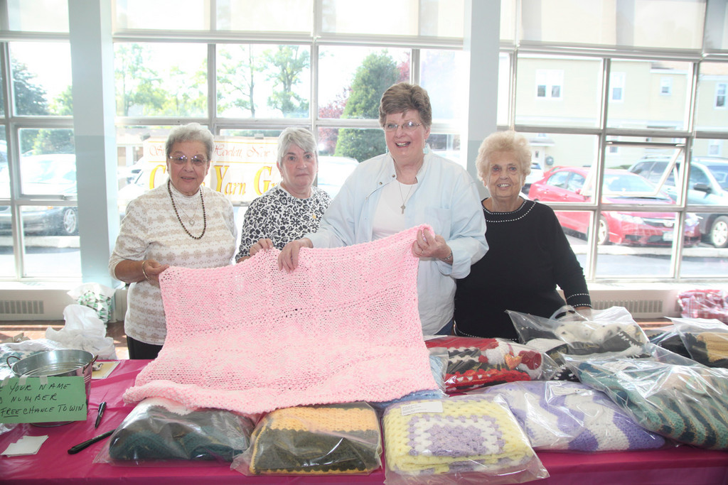 St. Joseph's Creative Yarn Group, Dolores Gilombardo, Joan Grossman, Gery DiDomenico, and Francis Macioce, highlighted one of their knitted creations.