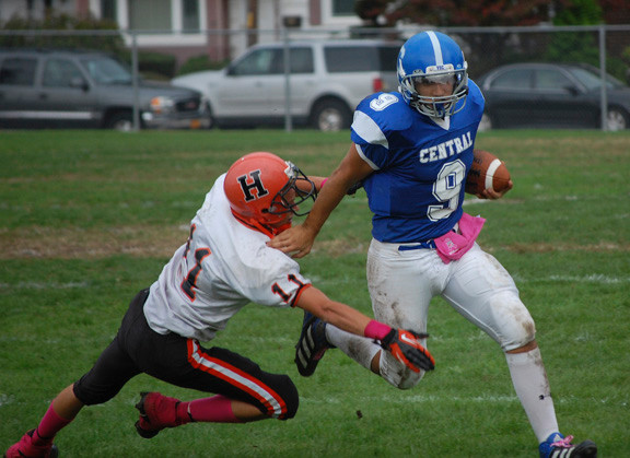 Central quarterback Vito Friscia breaks past Hicksville defender Joseph Collazo to pick up some yards in the Eagles 27-0 win at Firemen's Field.
