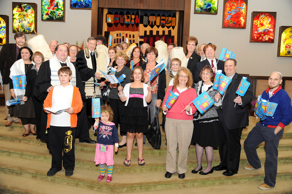 Temple Beth Am of Merrick-Bellmore recently marked Simchat Torah, a Jewish holiday that celebrates the Torah, Judaism's most sacred text, which contains the five books of Moses and is the source of the Ten Commandments. Above, Rabbi Ronald Brown, eighth from left, and congregants gathered after dancing and marching with Torahs in hand around the synagogue.