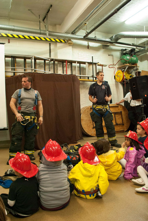 Firemen John Fitzpatrick, left, and John O'Brien showed youngsters the equipment they carry to rescue calls.