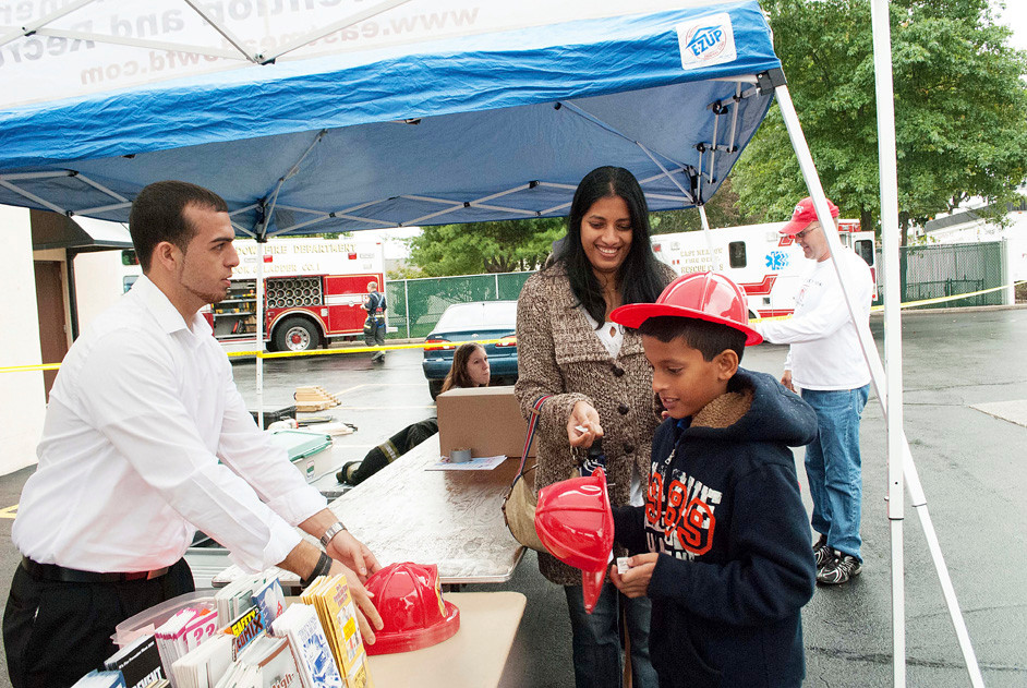 Joe Bonura, left, volunteered by handing out pamphlets and fireman helmets. Noel Manalil, 9, pictured with his mother, Reena, picked up an extra helmet for 5 year old sister, not pictured.