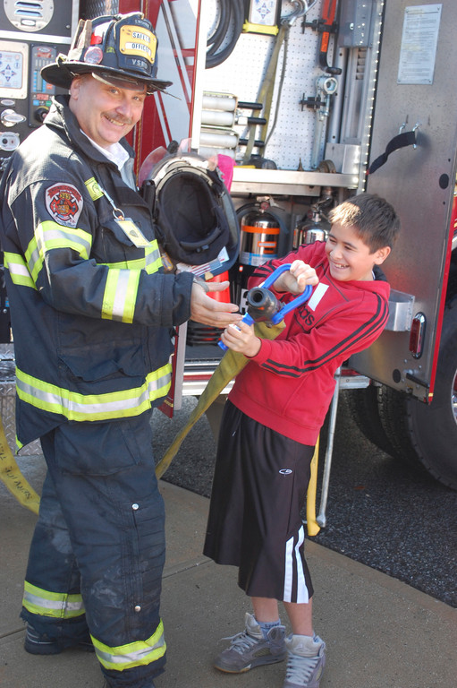 Kevin Paez, a sixth-grader at the Robert W. Carbonaro School, checked out the equipment that real firefighters use with Valley Stream Fire Department Safety Officer Michael Laxton on Oct. 10.