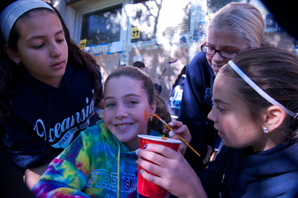 Sabrina Foster, left, Olivia Burnside, second from right, and Lucia Alamia practiced their skills on Casandra Dolan.