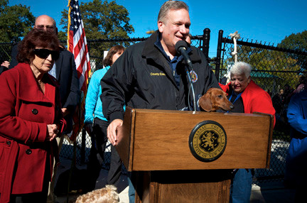 County Executive Ed Mangano, joined by one of his dachshunds,  welcomed dog owners to the newest pet-friendly park. Legislator Norma   Gonsalves, left, was also in attendance.