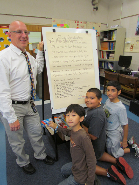 Students Paul Choi, Andrew Nunez and Rahim Akhter signed their class constitution during a lesson on government taught by Joe Targove, pictured left.