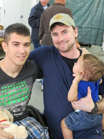 Marine CPL Marcus Dandrea, left, with former Navy Corpsman Micah Ambrose, who is holding his namesake, Micah Dandrea.