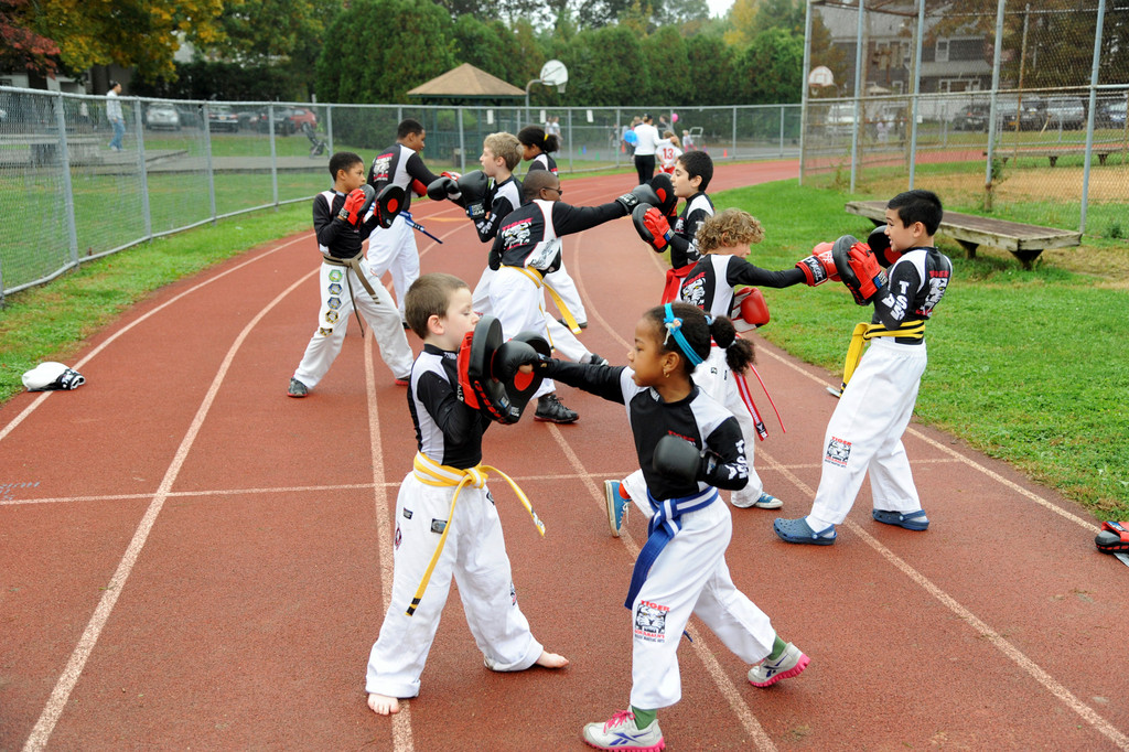 Tiger Schulman School gives a karate demo on the track around the football field.