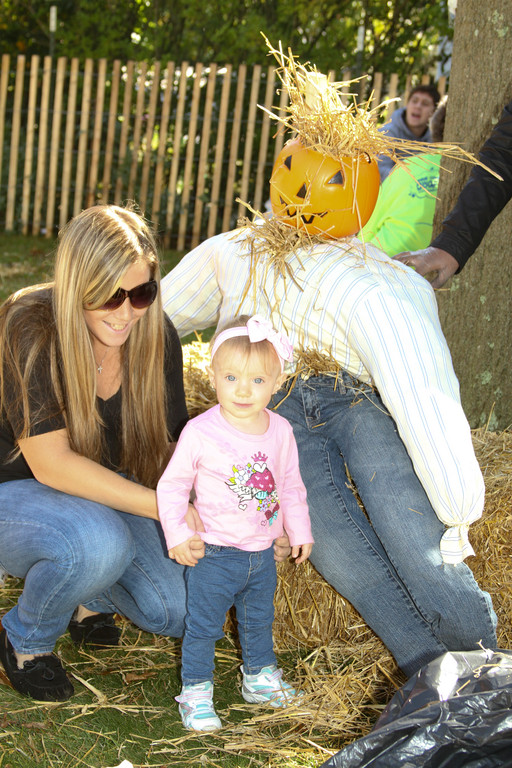 Scarecrow making was for all ages as Michelle Ritterman and 16-month-old Adriana Lauritie pose by their creation.