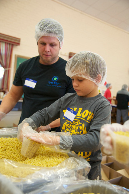 Tim and Peyton Hopper scoop and measure pasta for the outreach progam at the Oceanside Lutheran Church.