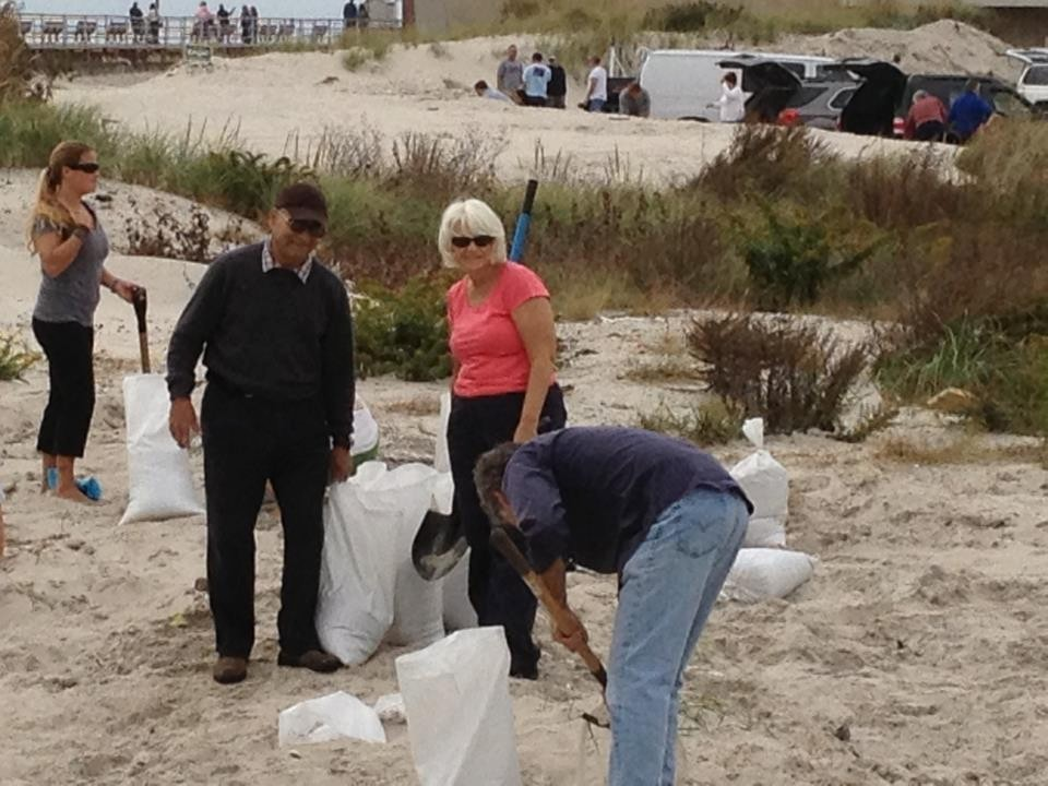 City Council President Len Torres, left, with his wife Beth, filling sandbags on the beach on Saturday.