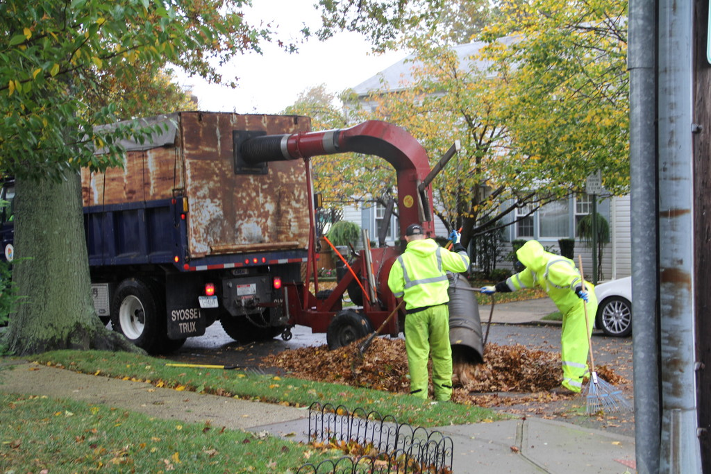 A crew sucked up leaves from a storm drain in the Village of Malverne.