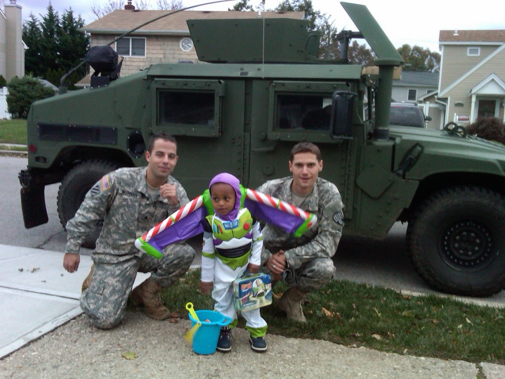 While on duty checking up on locals in the aftermath of Hurricane Sandy, National Guard specialists Josh Brennan, left, and Brian McGee bumped into another fellow lifesaver, Buzz Lightyear, on Halloween.