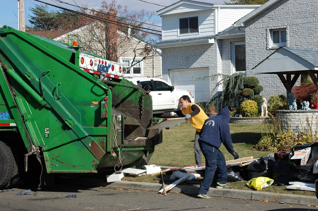 Workers From Sanitary District No. 1 picked up damaged possessions lining Heatherfield Road and other streets on Monday in the Mill Brook neighborhood, which suffered coastal flooding from Hurricane Sandy.