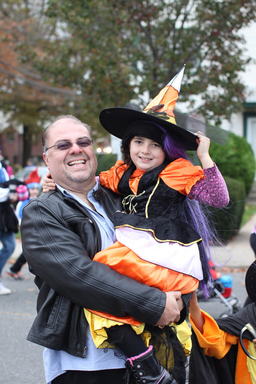 Brianna Rolon, 7, in costume as a witch, with her father, JR, during the parade.