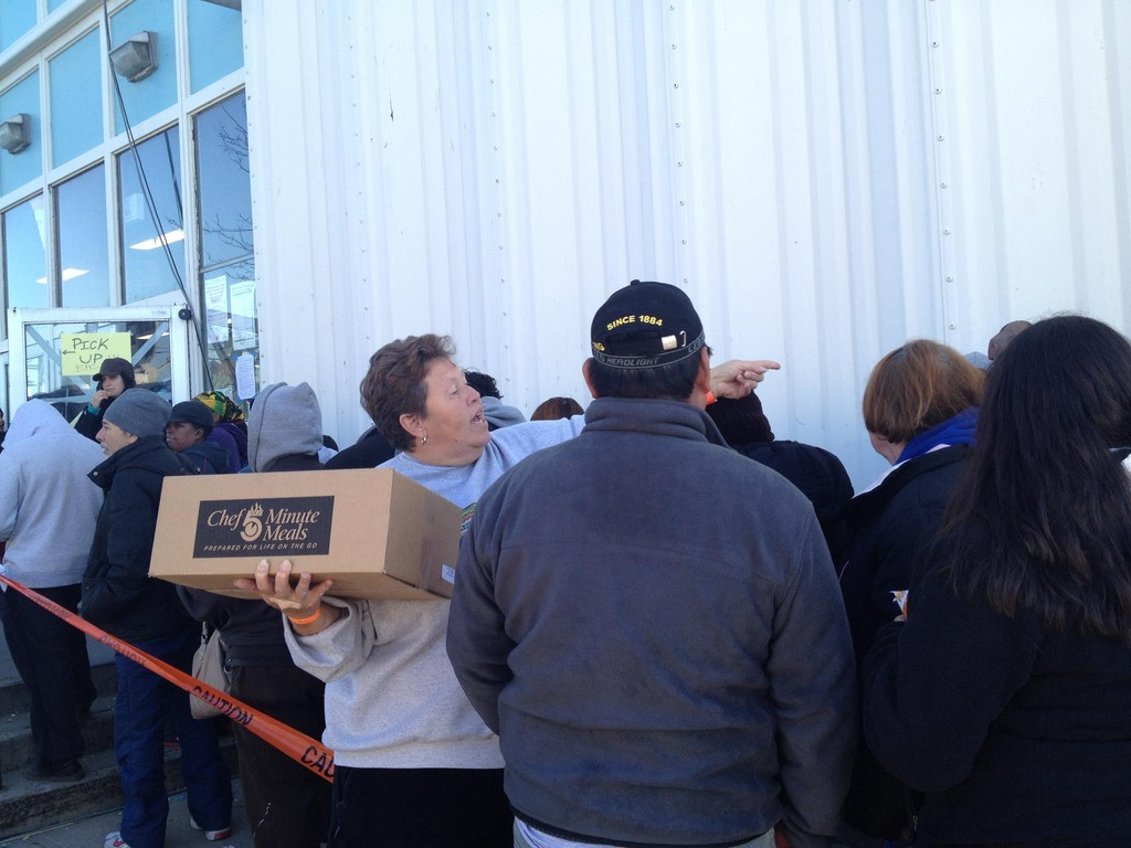 Lucy Centeno gave out ready-to-eat meals to fellow residents waiting on line to file FEMA claims at the ice arena.