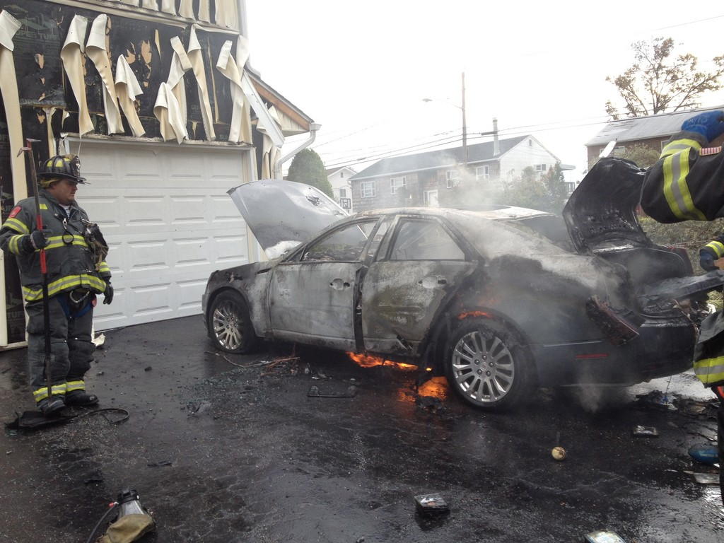 After Sandy struck, Merrick Fire Department volunteers extinguished this car fire, caused when a resident attempted to start the car, which had been submerged in floodwaters.