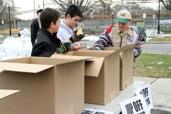 Valley Stream Troop 116 Boy Scouts, from left, Kevin Glaittli, David Glaittli and Chris Rafloer, packaged food that was collected by the village during a drive last Saturday to benefit the victims of Hurricane Sandy.