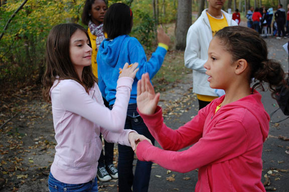 Memorial Junior High School seventh graders Gabrielle Sturek, left, and Genesis Rodriguez practice their celebration handshake during the Oct. 26 Explorations program at Valley Stream State Park.
