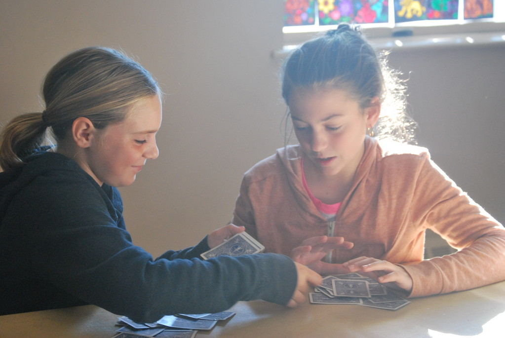 Erica Pagano, 10, left, and Madelyne Schmitt, 12, played cards at the firehouse, where they and their families have stayed since the storm damaged their homes.