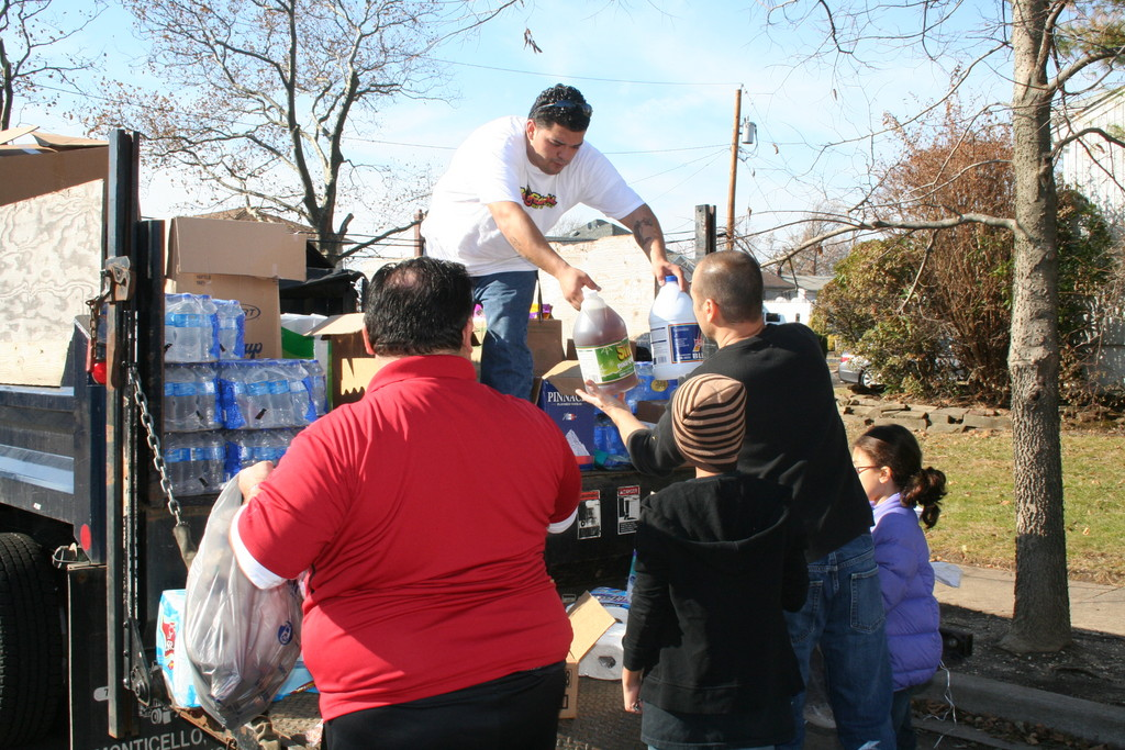 Five Towns Community Center counselor Felipe Plaza hands cleaning supplies to Inwood resident Ralph Cancelliere.