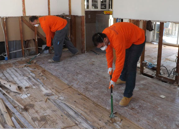 Members of Samartian's Purse, a faith-based group from Boone, N.C., are providing hurricane relief to the South Shore of Long Island. Pictured are brothers Gianni, right, and Sam Maraia, digging up a floor in Long Beach.