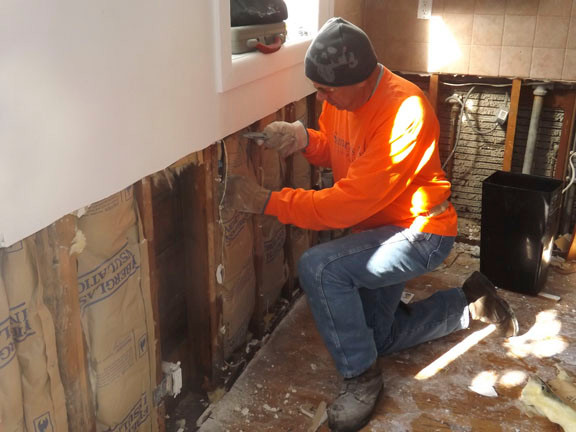 Joe Wasser, of St. Louis, Miss. stripped insulation from the kitchen walls.
