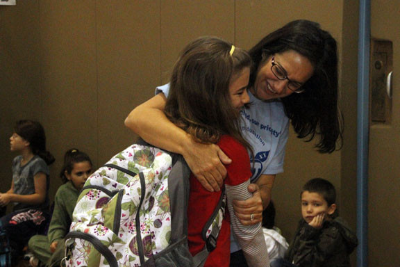Oceanside School 8 teacher Stefanie Cook gave student Lara Rhatiga a hug as schools reopened on Tuesday after being closed for 10 days. Due to the damage at School 8, its students are attending classes at School 6.