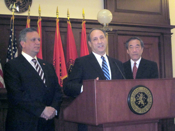 Bruce Ratner, the CEO of Forest City Ratner Companies, stands at the lectern, joined to his left by County Executive Ed Mangano and New York Islanders owner Charles Wang