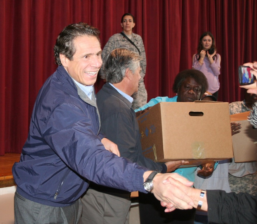 Gov. Cuomo, left, shook a Five Towns resident's hand as State Sen. Dean Skelos handed a meal to a family at the Community Center.