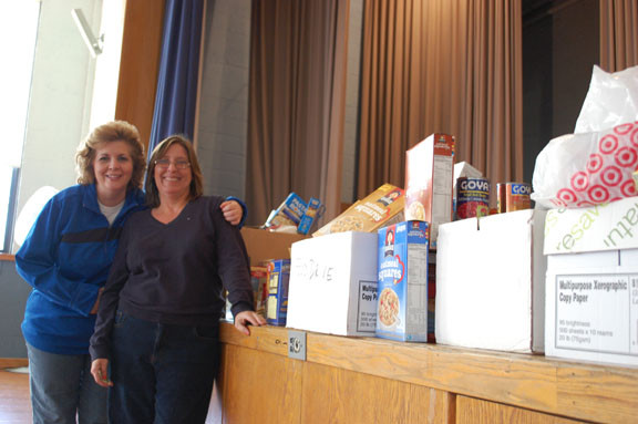 School Nurse Maria Griffin, left, and Grace United Methodist Church food drive coordinator Theresa DiSalvo with the donations.