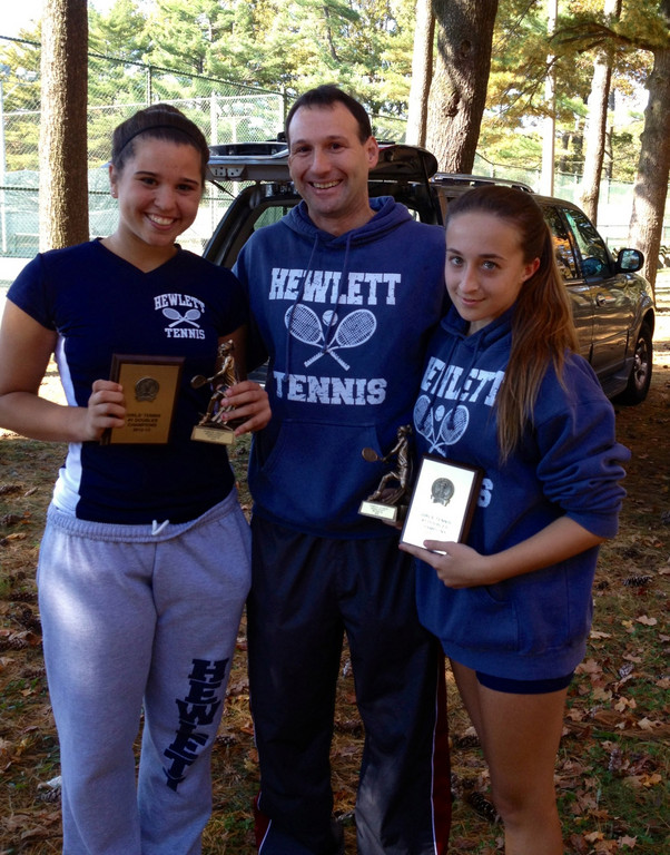 Hewlett tennis players Gabby Leon, left, and Veronika Paikin, right, flank coach Ron Remick after capturing their second straight Nassau County doubles crown.