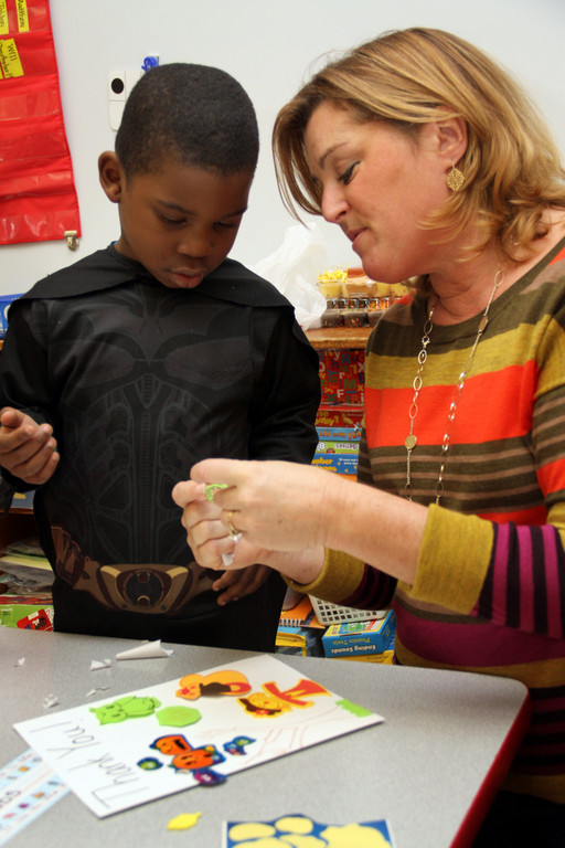 Kindergarten teacher Karen Feltkamp helps Kamar Robbs with his card at Riverside Elementary.