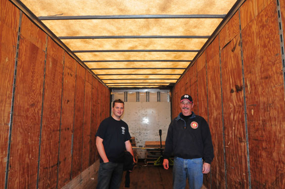 Broome County firemen Justin Petcosky and Bill Maguire stand inside the empty 53-foot truck that was filled with  donated water, food, pet food and clothing from seven different fire departments in their county.
