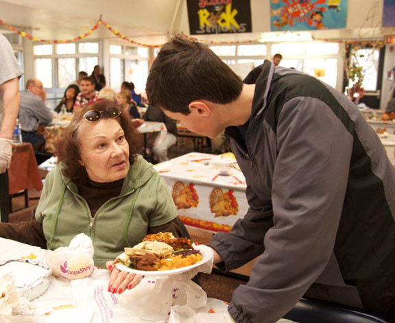 Michael Pociess served food to Beverly Seidman at a Thanksgiving meal hosted at Oceanside High School last week. The meal was sponsored by Oceanside Community Service, which collected and cooked food for hundreds of residents.