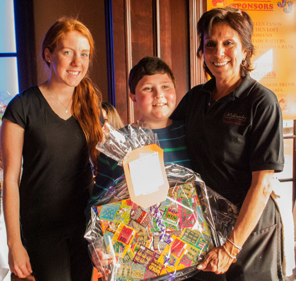 "Joshua Wangel, center, helped McQuade staffers Brittany O' Connor, left, and Rose Casaceli carry the ""NY Lottery"" prize."
