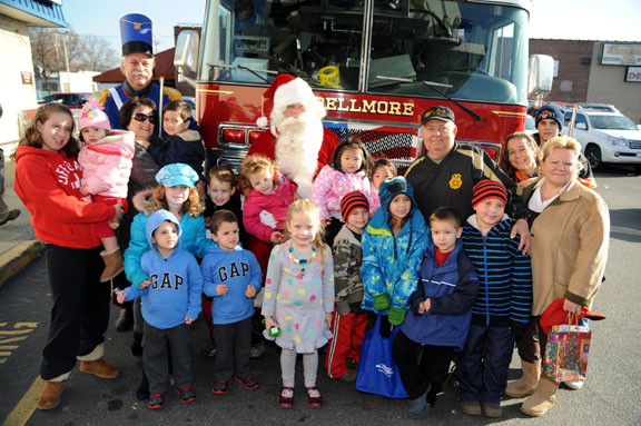 "Members of the Chamber of Commerce of the Bellmores introduced local children to Santa at each of the four stops along his ""run."""