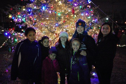 Children gathered around the Christmas tree that was lit up for the first time this holiday season last Friday night outside of Village Hall.